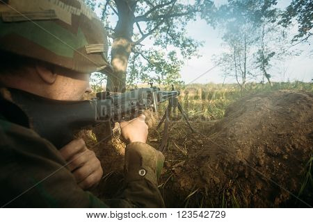 Teryuha, Belarus - October 4, 2015: Hidden unidentified re-enactor dressed as World War II german wehrmacht soldier aiming a machine gun at enemy from trench in fog
