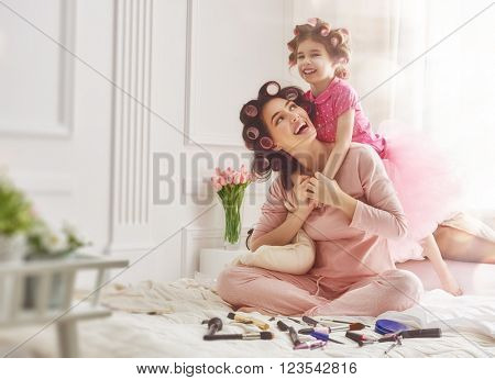 Happy loving family. Mother and daughter are doing hair and having fun. Mother and her child girl playing and hugging.
