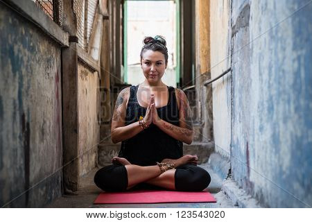 Pretty woman enjoying yoga in dilapidating building