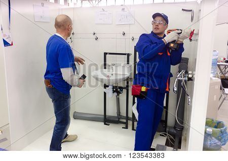 Tyumen, Russia - March 24, 2016: Open championship of professional skill among youth. World skills Russia Tyumen - 2016. Young plumber installs equipment for bathroom