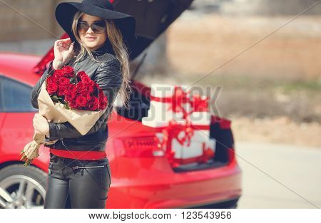The young woman, the blonde with a thick long hair, in sun glasses, a black leather jacket and black leather trousers, in a black hat with big fields, with a big bouquet of scarlet roses poses near the red car loaded by gift boxes