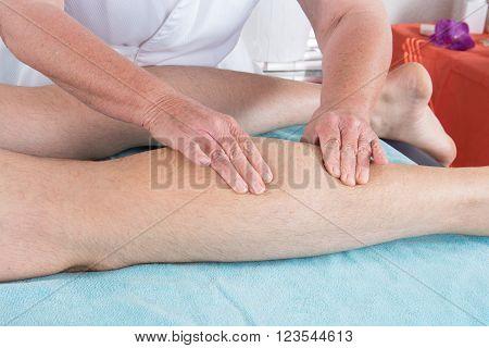 Horizontal view of masseur massaging female calf