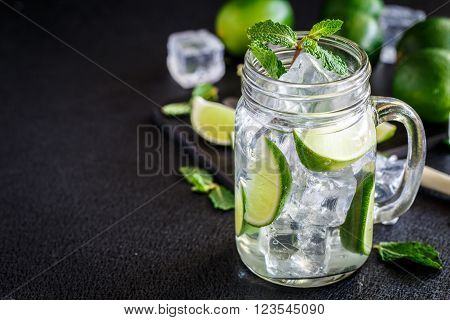 Cold drink with lime and mint in a glass