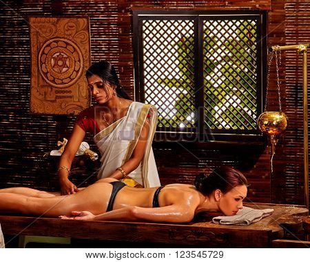 Young woman having Ayurveda spa treatment in India salon.
