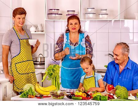 Family child with father cooking at kitchen. Grandfather and grandmother.