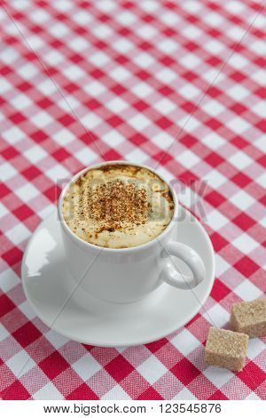 Black coffee with crema in a white porcelain cup and cane sugar on a background of red and white checkered cloth