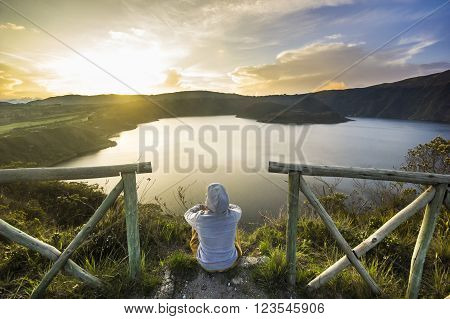 girl sitting on a edge of crater with lake inside at sunset in ecuador with little fence