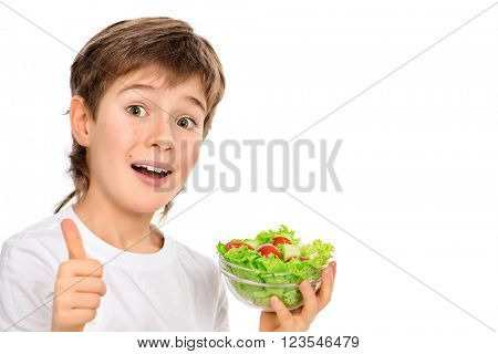 A nine year old boy holding fresh vegetable salad and showing a thumb. Healthy eating. Isolated over white.