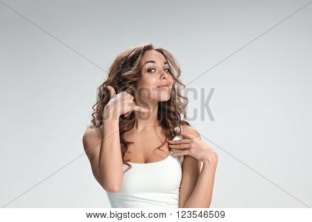 The young woman's portrait with different happy emotions on gray background. concept of communication by mobile phone