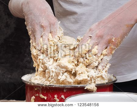 The process of kneading dough. human hands Close. The dough is made of flour. Kitchen pasuda - red pot