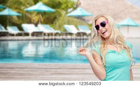 travel, tourism, vacation and people concept - smiling young woman or teenage girl in sunglasses holding her strand of hair over swimming pool on beach with sunbeds and parasol background