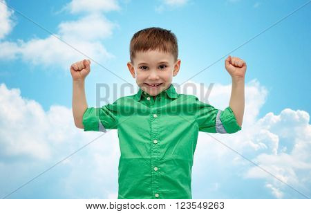 childhood, power, gesture and people concept - happy smiling little boy with raised hands showing his power  over blue sky and clouds background