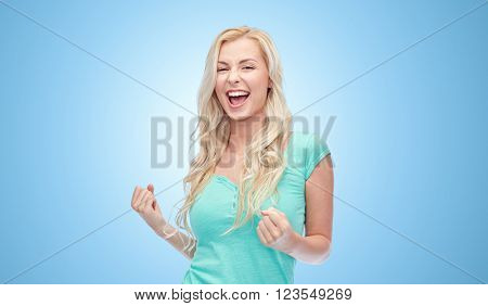 emotions, expressions, success and people concept - happy young woman or teenage girl celebrating victory over blue background