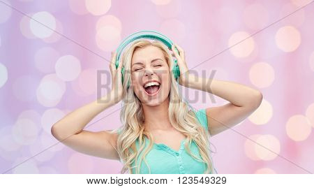 music, technology and people concept - happy young woman or teenage girl with headphones singing song over pink holidays lights background