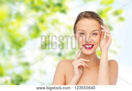 beauty, cosmetics, people and health concept - smiling young woman with pink lipstick on lips touching her face over green natural background
