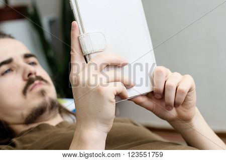 Lying Caucasian bearded man reading ebook in white cover