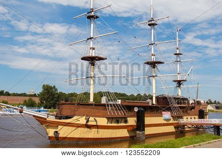 Veliky Novgorod, Russia - July 3, 2015: beautiful sailing ship moored to the shore.  Ship on a background of clouds. Inspiration travel. Romance of the seas ship with sails.
