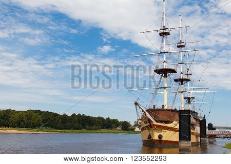 Veliky Novgorod, Russia - July 3, 2015: sailing frigate moored to the shore. Beautiful ship on a background of clouds. Inspiration travel. Romance of the seas ship with sails.