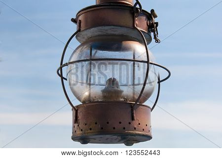 Vintage marine lantern with a wick. Rare external lamp on the on a sailboat. Something old for Inspiration of travel. Romance of the seas ship with sails. Attribute ancient mariners and pirates.