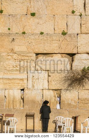 Orthodox Jewish man prays in the wailing wall of Jerusalem, Israel