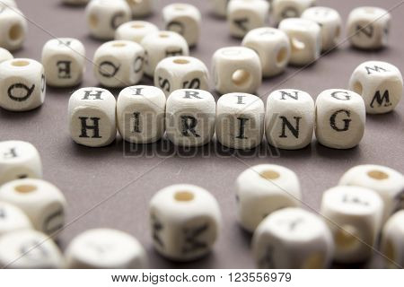 HIRING word written on wood block. Wooden Abc. ** Note: Shallow depth of field