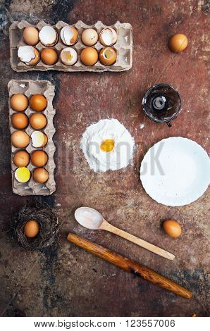 Baking cake ingredients - bowl flour eggs egg whites foam eggbeate on wood chalkboard from above. Cooking course or kitchen mess poster concept. Flat lay. Rustic style