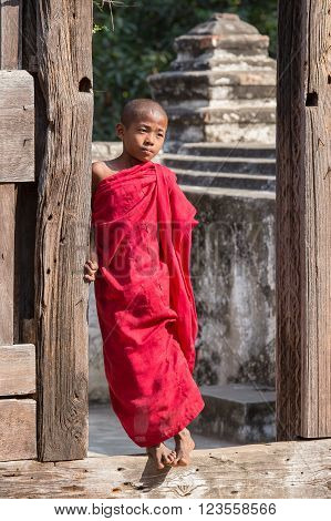 MANDALAY, MYANMAR - JANUARY 17, 2016 : Young monk standing and looking at Shwenandaw Monastery is built in the traditional Burmese architectural style