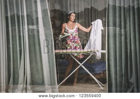 young woman ironing clothes at home, horizontal view through window