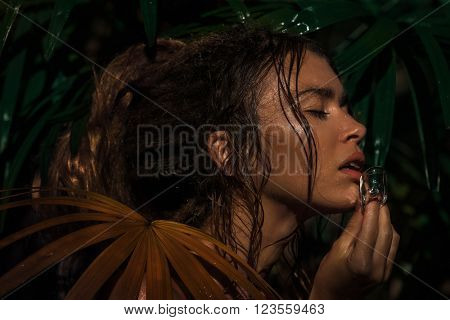Portrait of young caucasian woman with ice in a rain forest