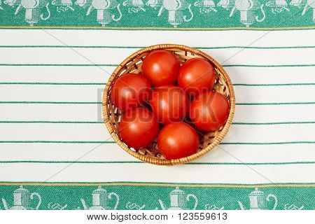 Several red tomato lie in the wattled plate standing on a towel