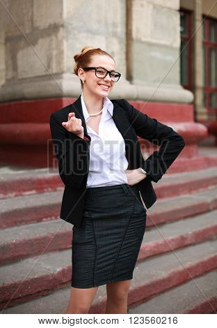 Cheerful student girl pointing a finger in a business suit on a university background