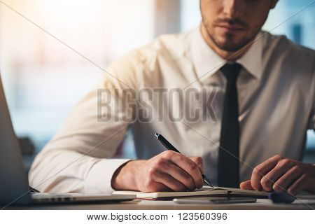 Deep in his work. Close-up part of young man writing in his notebook while sitting at his working place