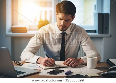 Creativity at work. Pensive young handsome man writing in his notebook while sitting at his working place