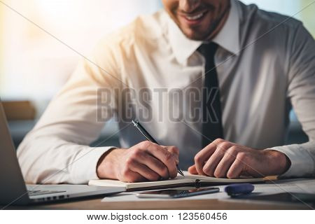 Working with pleasure. Close-up part of young man writing in his notebook with smile while sitting at his working place