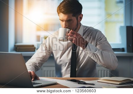 Sip of fresh coffee at work. Pensive young handsome man using his laptop and drinking coffee while sitting at his working place
