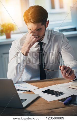 Feeling tired. Frustrated young handsome man looking exhausted while sitting at his working place