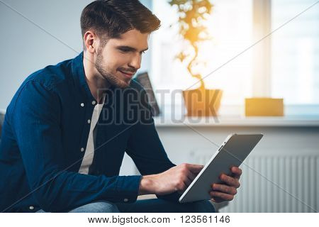 Technologies bring joy. Side view of handsome young man using his digital tablet with smile while sitting on the couch at home