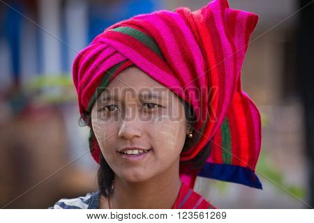 INLE LAKE MYANMAR - JANUARY 12 2016: Unidentified young Myanmar girl with thanaka on her smile face is happiness. Thanaka is a yellowish-white cosmetic paste made from ground bark.
