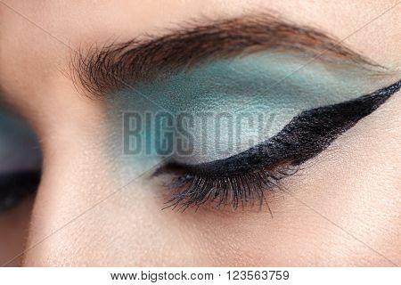 Close-up of woman eye with beautiful turquoise smokey eyes with black long arrow makeup. Modern fashion make-up.