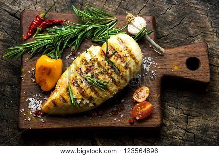 Grilled chicken breast with vegetables on wooden background