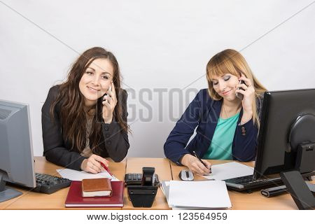 Two Girls In The Office Talking On Mobile Phones