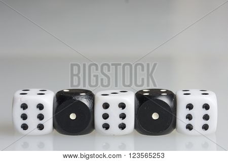 Dice. Playing cubes. Cubes white with a value of six points arranged in a row. Alternating with cubes of black color with a value of one point. On a white background. There is room for text.