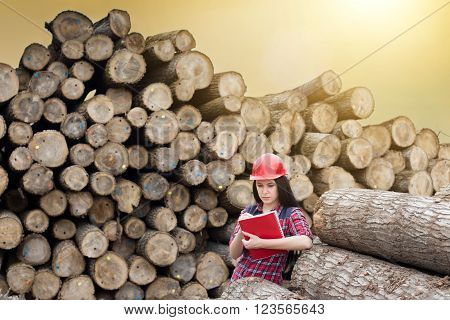 Female Forest Engineer Beside Logs