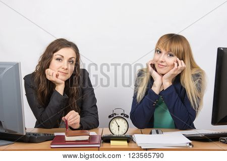 Two Girls In The Office Waiting For The End Of Working Hours On The Clock