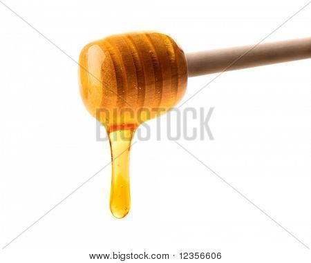 wooden honey dipper with a stream of honey
