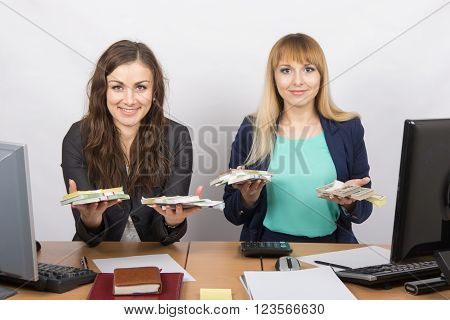 Two Office Staff Member At The Table Are Holding A Pack Of Money