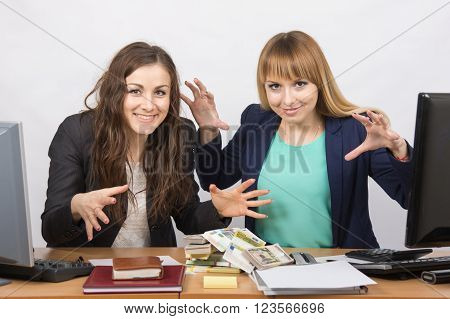 Two Office Employee Happy And Joyful Bent Over A Pile Of Money