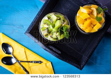 Dietetic dessert in the form of a fresh fruit salad with kiwi and peach with chia seeds and yoghurt served in a glass.Looking at the scene from above.