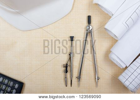 Architectural blueprints, blueprint rolls, compass divider, calculator, white safety on graph paper. Engineering tools view from the top. Copy space. Construction background