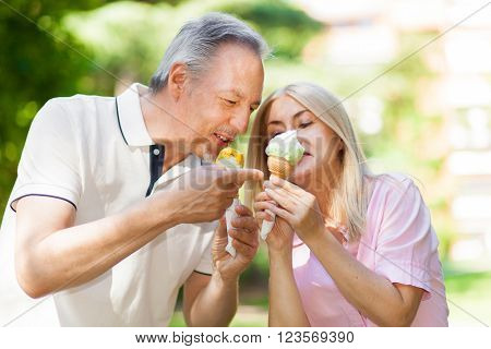 Happy couple eating an ice cream in a park